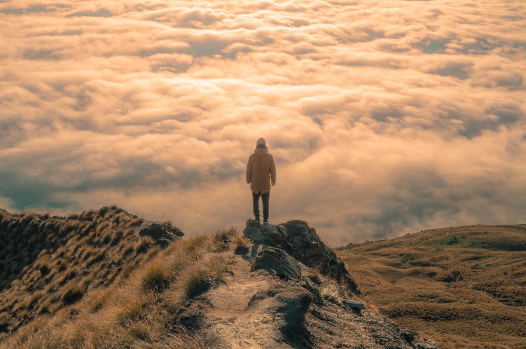 A person stands above the clouds